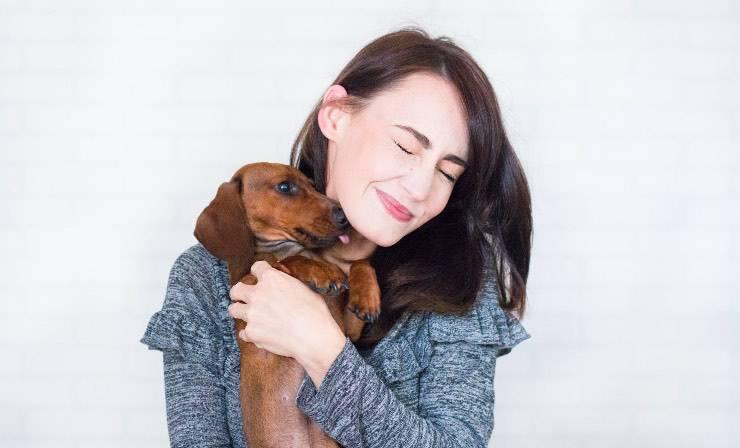 cane bassotto tedesco abbracciato a padrone