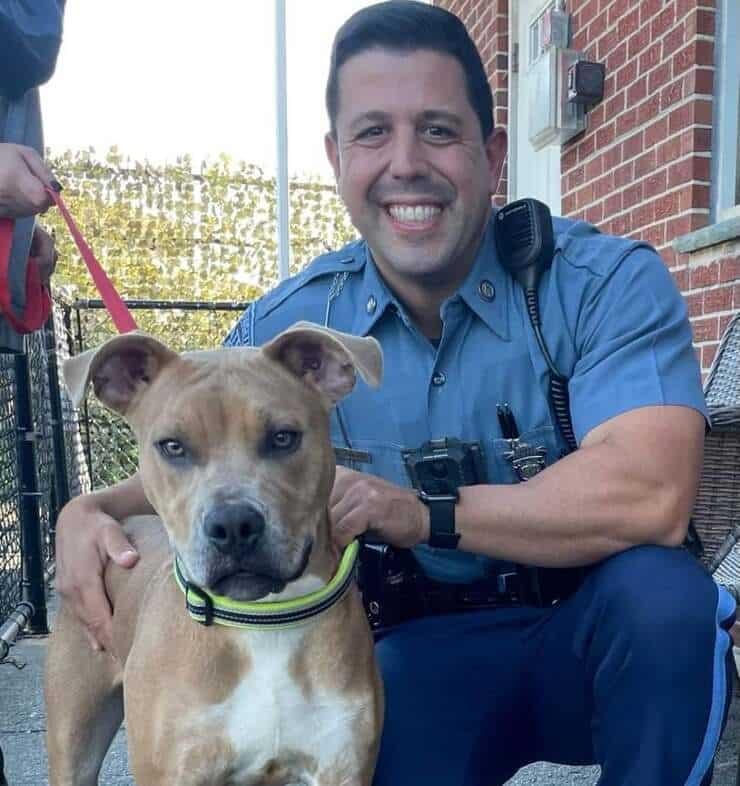 L'agente che ha portato in salvo il cane legato a catena in spiaggia in attesa della marea (Fotofacebook)